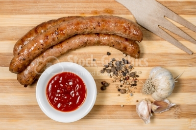 Sausages and ketchup on the wooden table