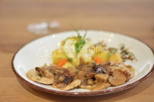 Sauteed mushrooms with a garnish of potatoes and peppers.