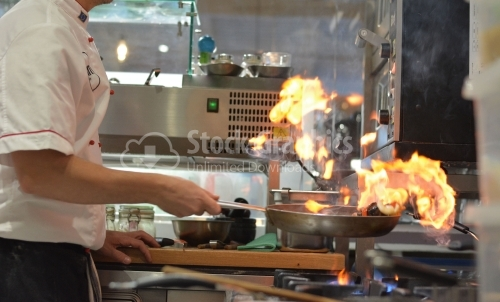 Seafood cooked with flame in a professional kitchen. The chef is photographed from one side.