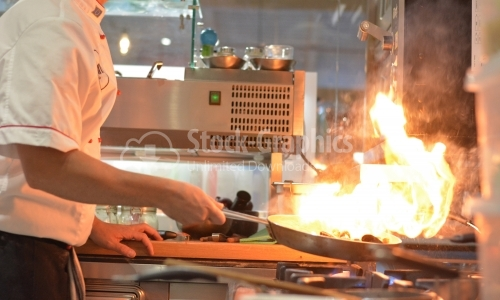 Seafood cooked with flame. The chef is photographed from the side.