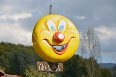 Smiling yellow balloon on blue sky background