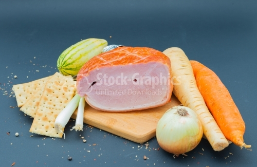 Smoked Prague ham on wooded cutboard with onion carot and cucume