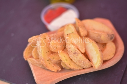 Spicy wedges potato on a wooden dish