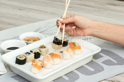 Sushi rolls aranged by a woman hand on a white plate