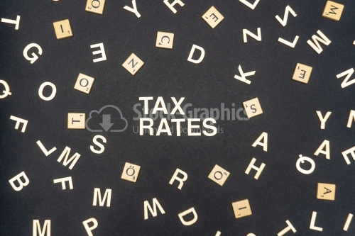 TAX RATES word written on dark paper background. TAX RATES text for your concepts