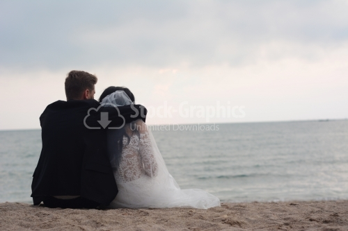 The bride and groom look back as they sit on the beach.
