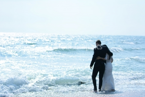 The embraced bride and groom enter the waves of the sea.
