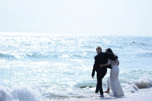 The embracing bride and groom play with their feet in the waves of the sea.