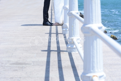 The feet of the groom and the bride on a walkway at sea.