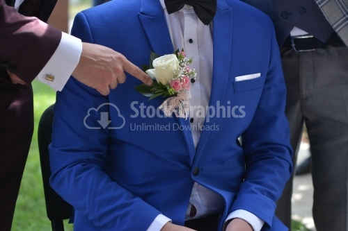 The groom sits on the chair and a man points to the flower in his chest.