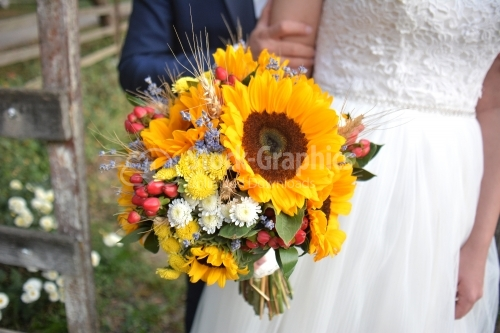 The groom, the bride and a bouquet of flowers. The sunflower is part of the wedding theme.