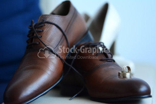 The groom's brown shoes and engraved gold wedding rings.