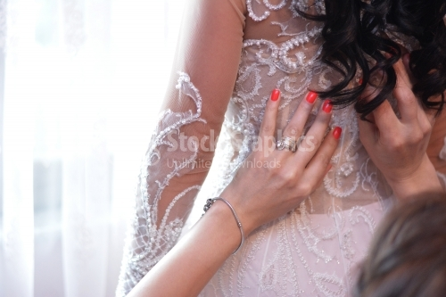 The lady with the red nails finishes a bride's dress.