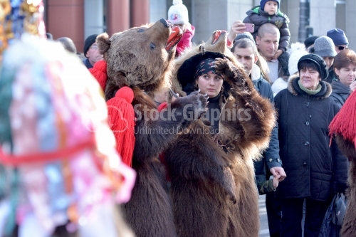 The young girl play the bear on the street. New Year's popular dance.