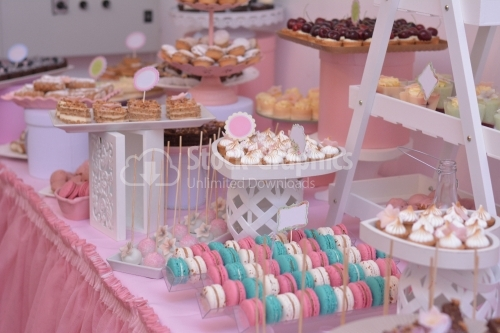 Trays with macarons and meringue, in a pink decor. Candy bar