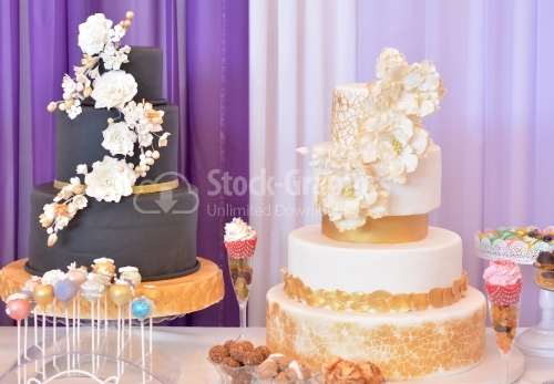 Two big cakes. cake covered with black marzipan, golden ribbon and beige flowers. White cake with golden decorations, large beige flowers, golden lace and golden leaves