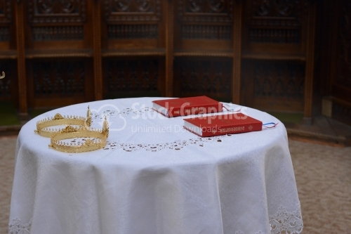 Two ceremonial crowns and two holy bibles as orthodox wedding accessories