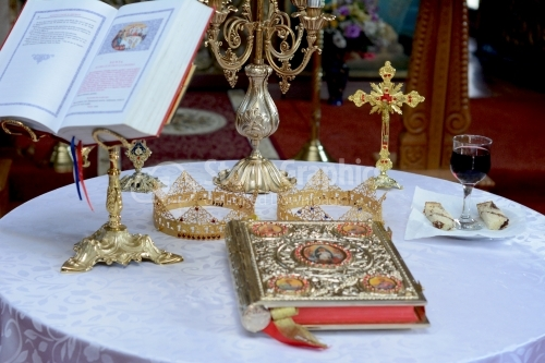Two crowns for a orthodox wedding ceremony , the bible and a glass of red wine