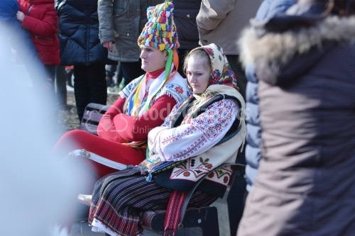 Two tired young people, dressed in romanian national costume at the winter festival. Authentic traditional from Romania