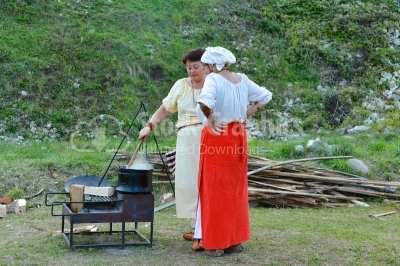 Two womens cooking food on a medieval festival