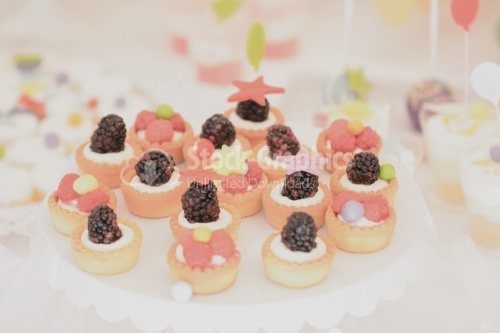 Vanilla cream mini tarts decorated with raspberries and blackberries