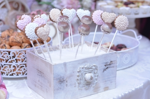 Various cake pops decorated with white and dark chocolate on a white-pink background