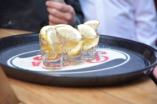 Vodka in shot glasses with lemon on the tray