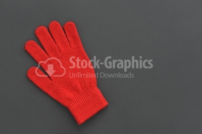 Warm woolen knitted glove on dark texture
