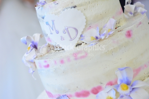 Wedding cake with white-purple flowers and the initials of letters M and D