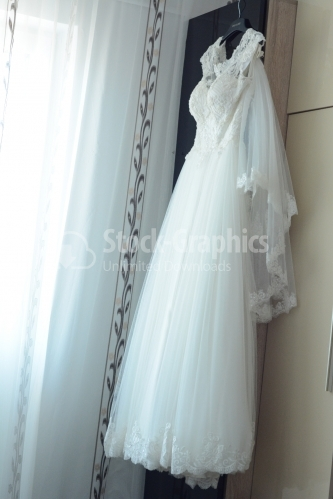 Wedding dress hanging from furniture.