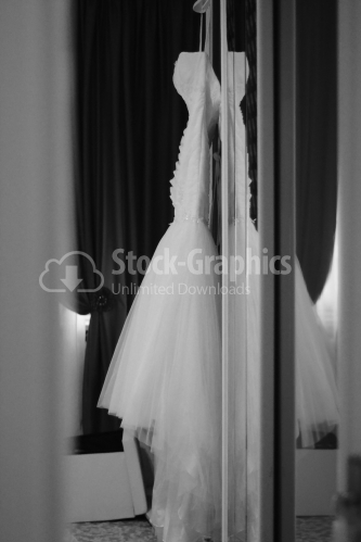 Wedding dress hanging from furniture. Black and white photography.