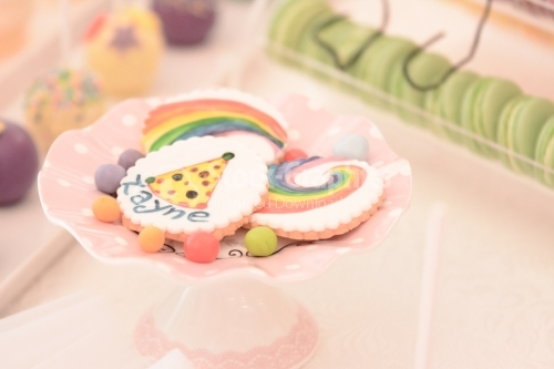 White cookies with colorful drawings; Rainbows and clown hats drawings