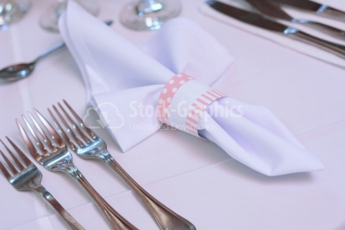 White towel with pink details placed on a wedding table