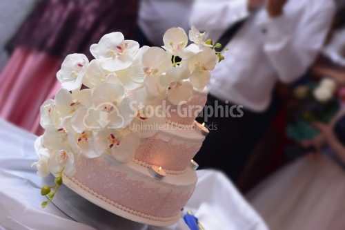 White wedding cake decorated with pink lace and white orchid