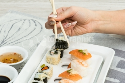 Woman hand arranging sushi on plate
