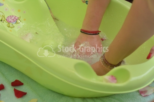 Woman with the hands on the green baby bathtub