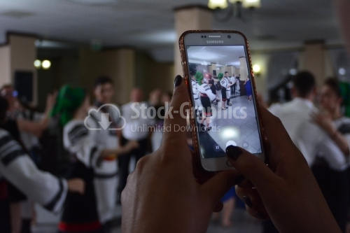 Young girl taking a photo on a wedding