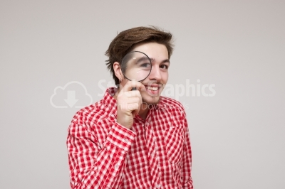 Young guy looking throug a magnifying glass