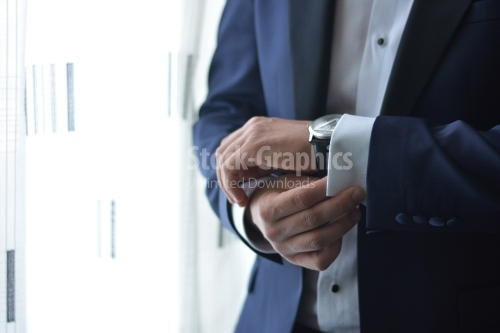 Young man puts his watch on his hand. Groom. Businessman.